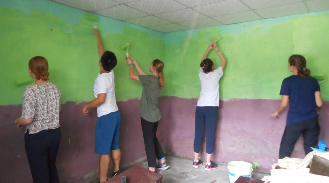 Jóvenes voluntarios pintando muros de una escuela en Nepal.
